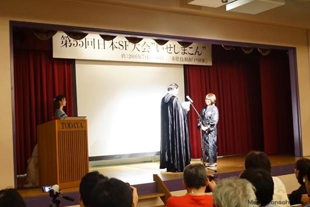 黒マント姿の、かとう暗黒星雲賞実行委員長から自由部門賞を授与される戸田家の女将さん。