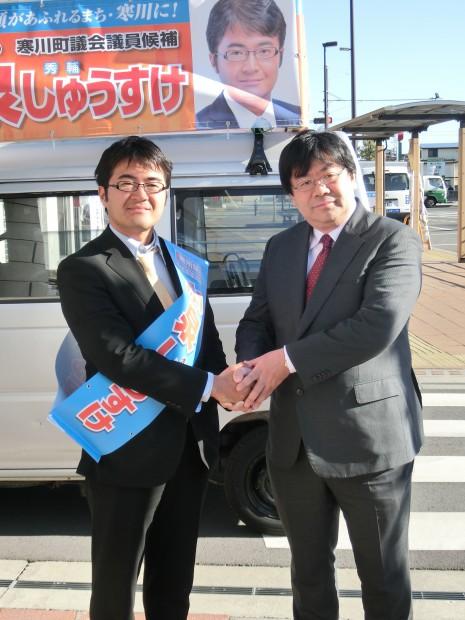 選挙カー前で固い握手をする小泉しゅうすけ氏(右)と山田太郎前参議院議員(左)。